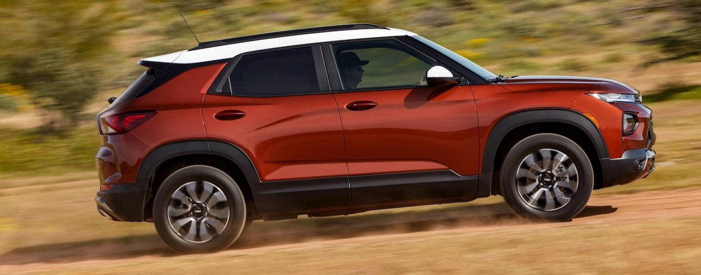 A red 2021 Chevy Trailblazer is shown from the side while it drives on a dirt road.
