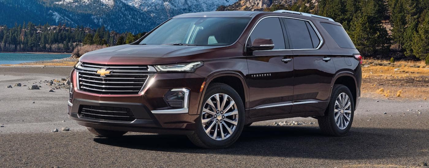 A newer Chevy SUV, a burgundy 2022 Chevy Traverse, is parked in front of a river and mountain.