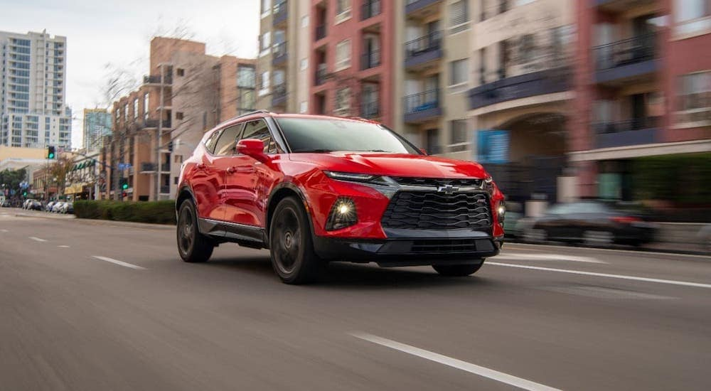 A red 2020 Chevy Blazer RS is driving on a city street.