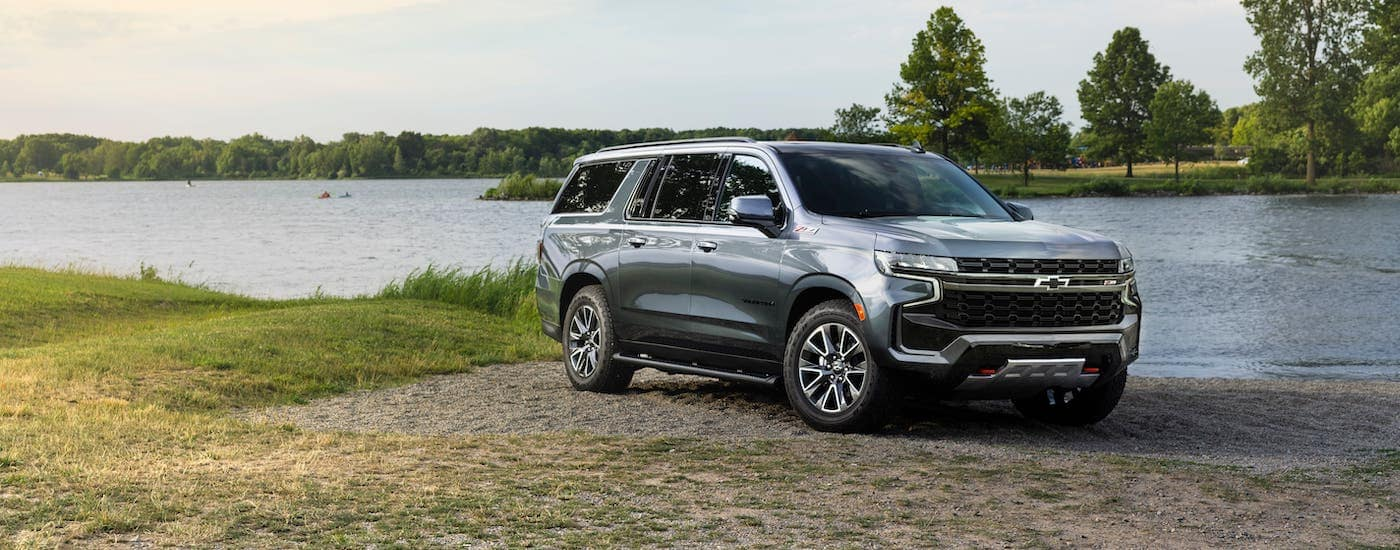 One of the newer Chevy SUVs, a gray 2021 Chevy Suburban Z71, is parked in front of a river near Indianapolis, IN.