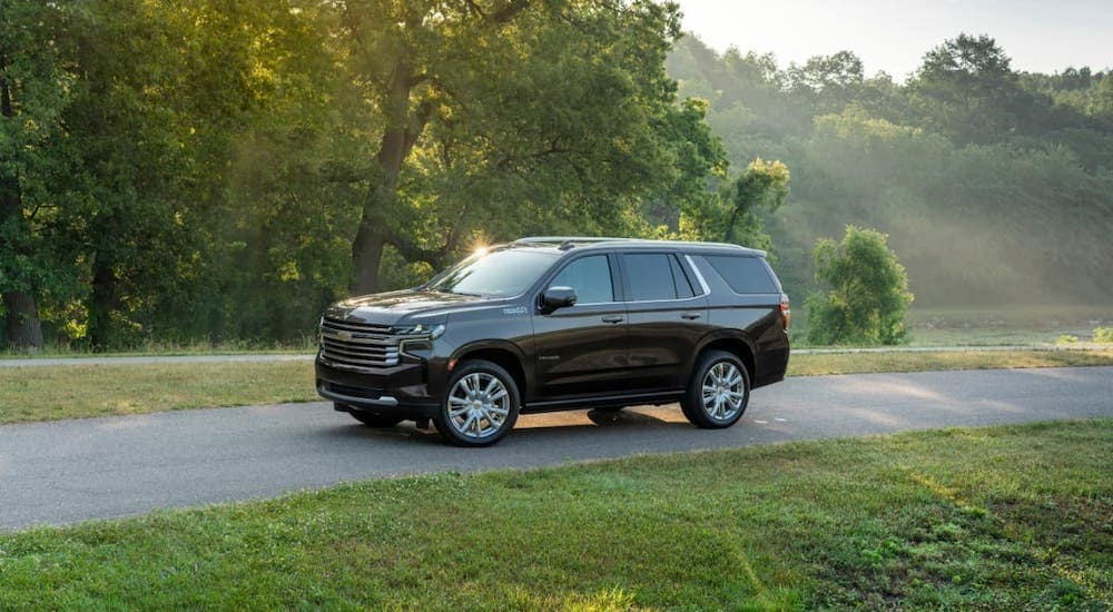 A black 2021 Chevy Tahoe High Country is driving on a road in front of trees.