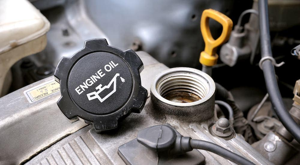 A closeup shows an oil cap on an engine that is removed during an Oil Change Near you around Indianapolis, IN.