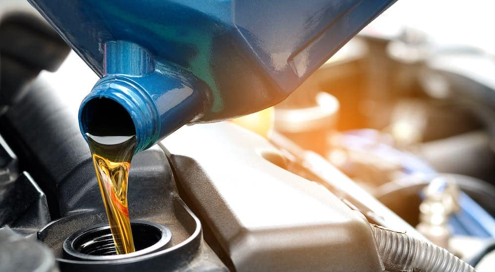 A closeup shows oil being poured into an engine as part of an oil change in Indianapolis, IN.