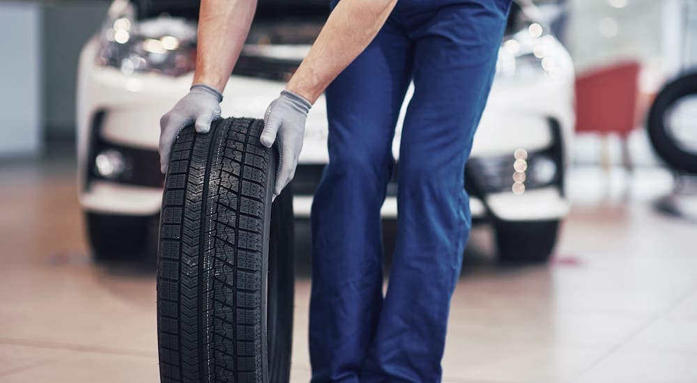 A mechanic is shown rolling a tire in front of a white car in an Indianapolis tire shop near me.