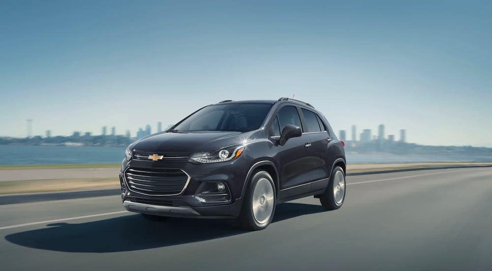 A gray 2020 Chevy Trax is driving away from a Chevrolet Dealer near Lawrence, Indiana, and away from a city.
