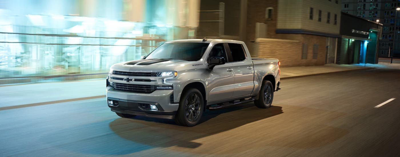A silver 2020 Chevy Silverado Rally Edition is driving on a city street at night.