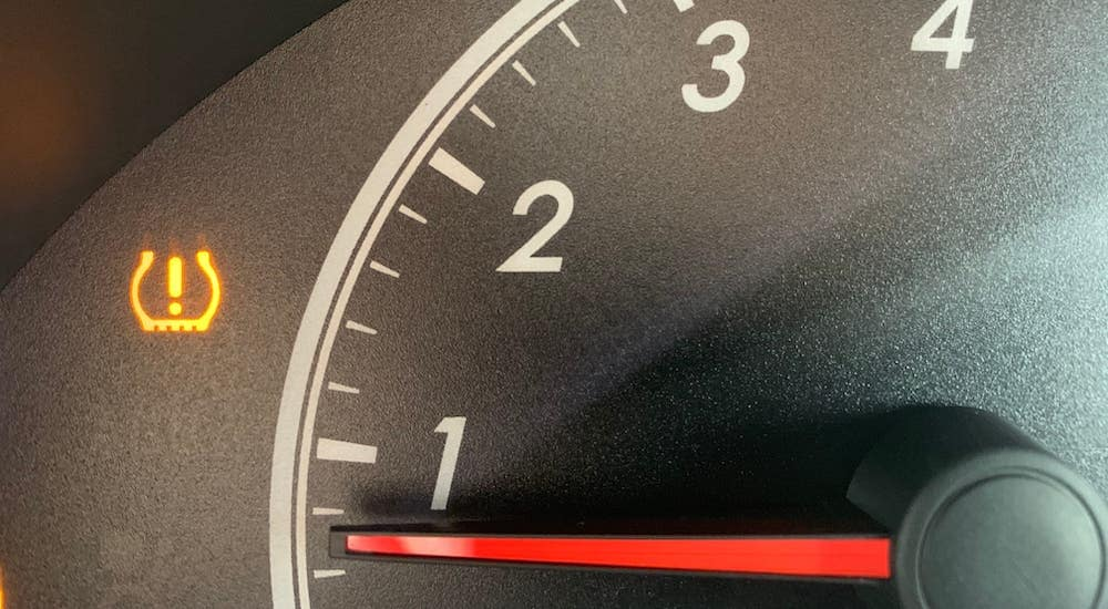 A closeup shows the tire pressure light on the information cluster on a car while being checked out at a tire shop near you.