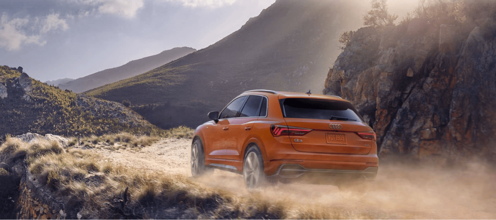 Audi Q3 stirring up dust on dirt road with mountains in distance