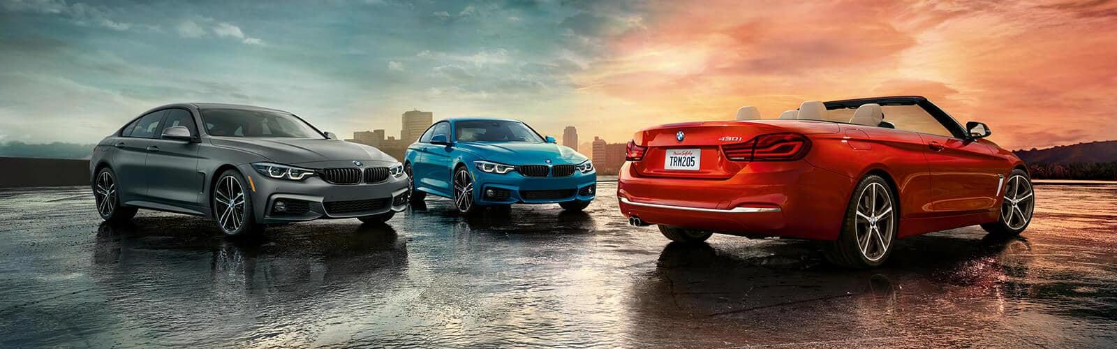three beautiful BMWs with sun setting behind
