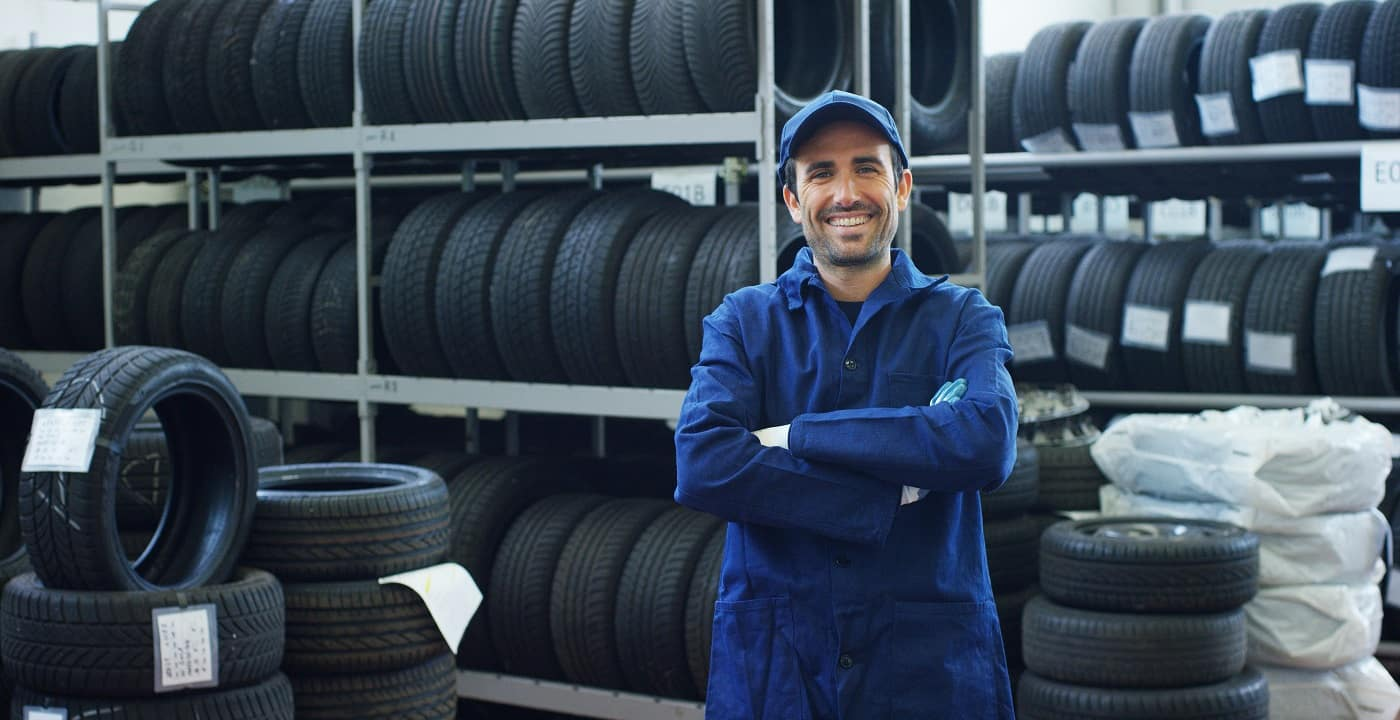 Mechanic Smiling in Front of Tires