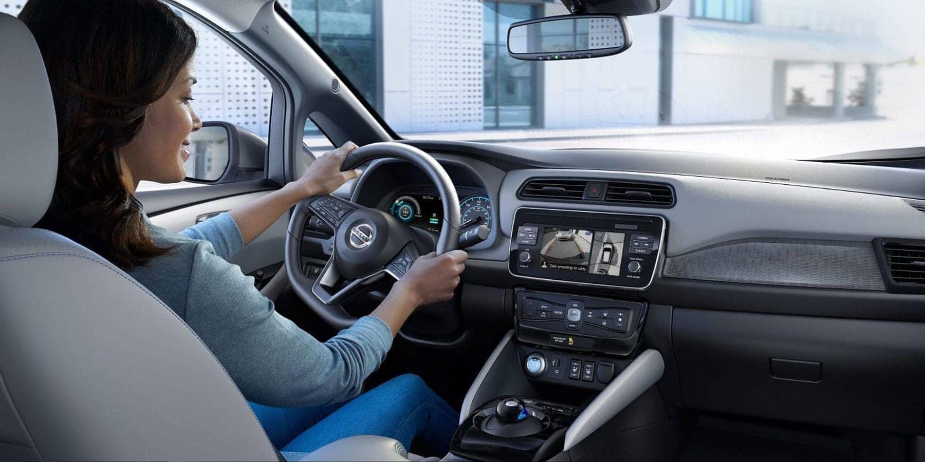 Woman driving a Nissan Leaf