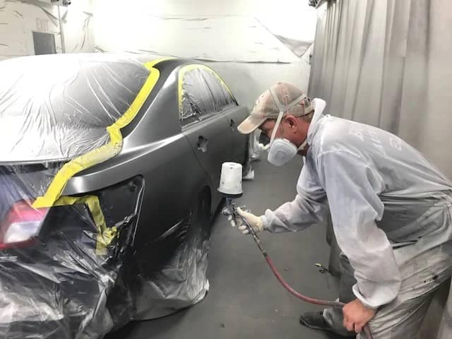 Tech painting a car
