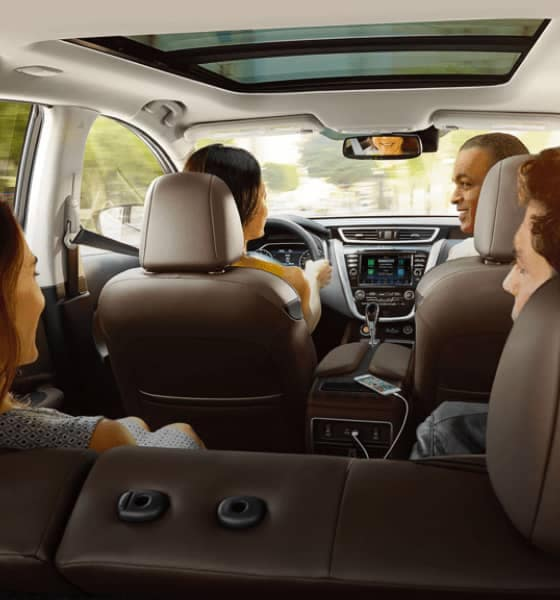 A group of people inside of a Nissan SUV