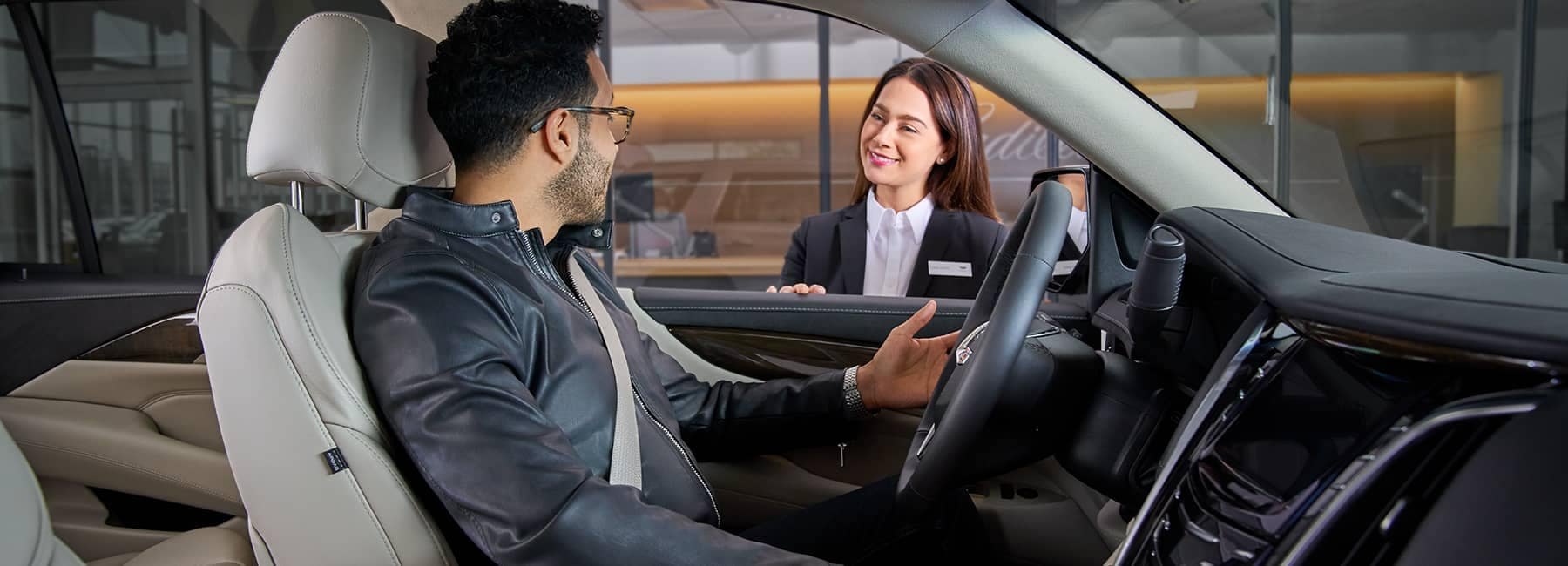 A man sitting in the drivers seat talking with a salesperson