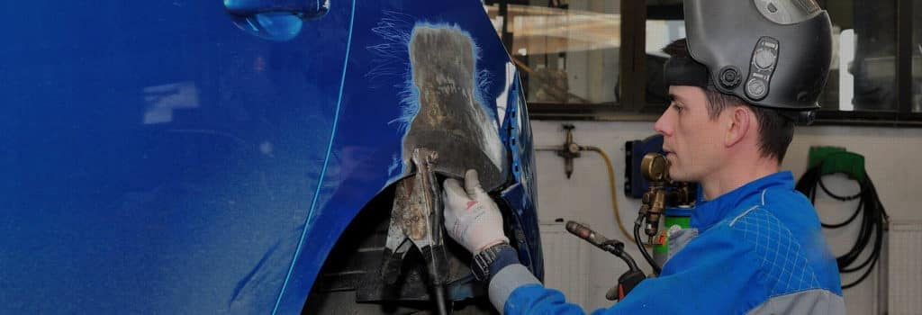 Man Fixing the Body of a Blue Car by Wheel