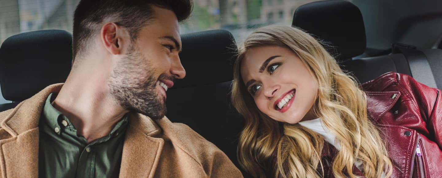 hero image of two people in a car smiling at each other