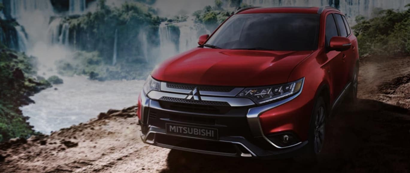 Red Mitsubishi Outlander sitting in front of a waterfall