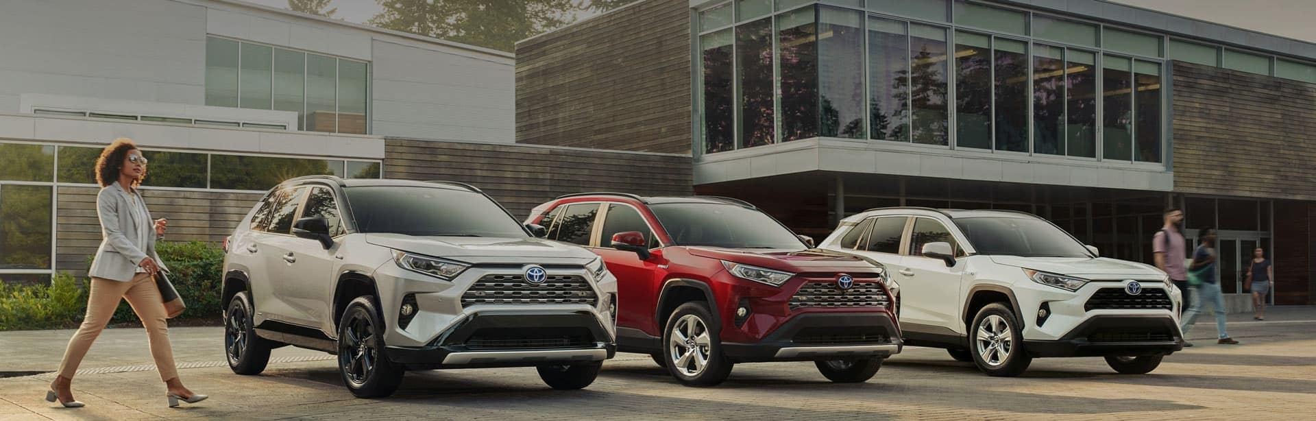 Three Toyota SUVs lined up in front of a building