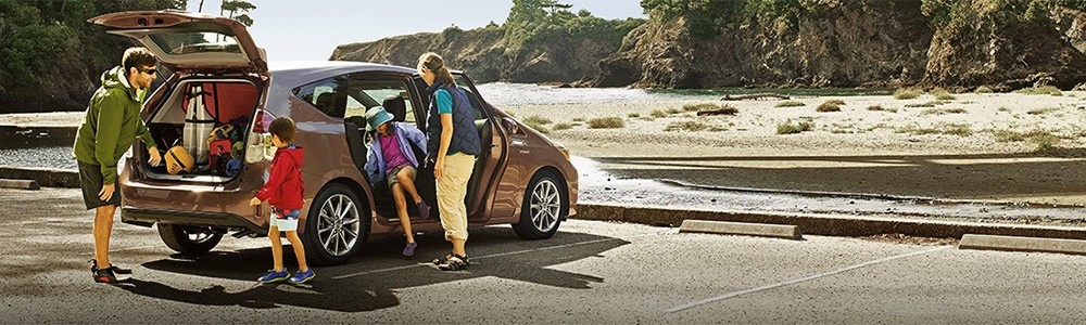Family loading gear into 2018 Toyota Prius v, part of the Toyota Hybrid Lineup