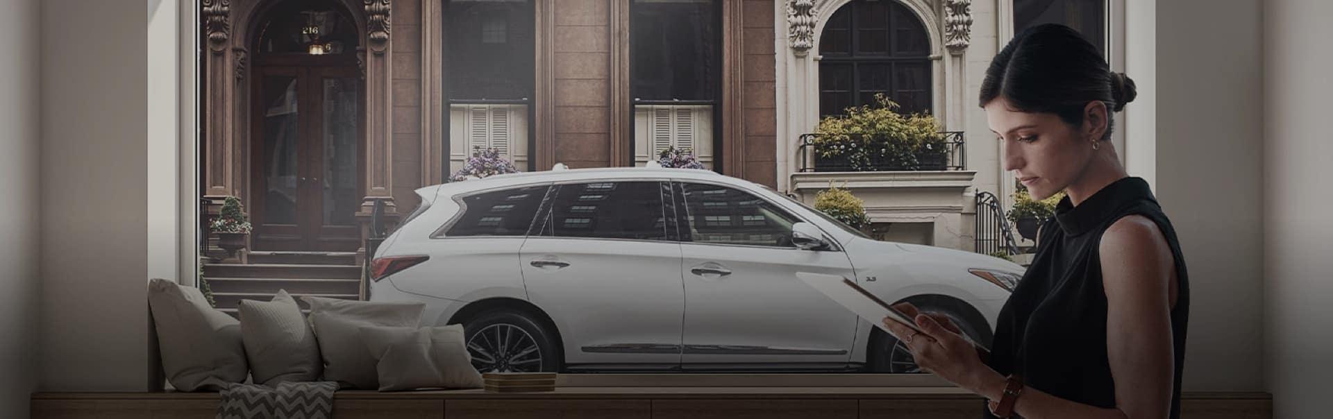 Women standing by window next to white luxury car