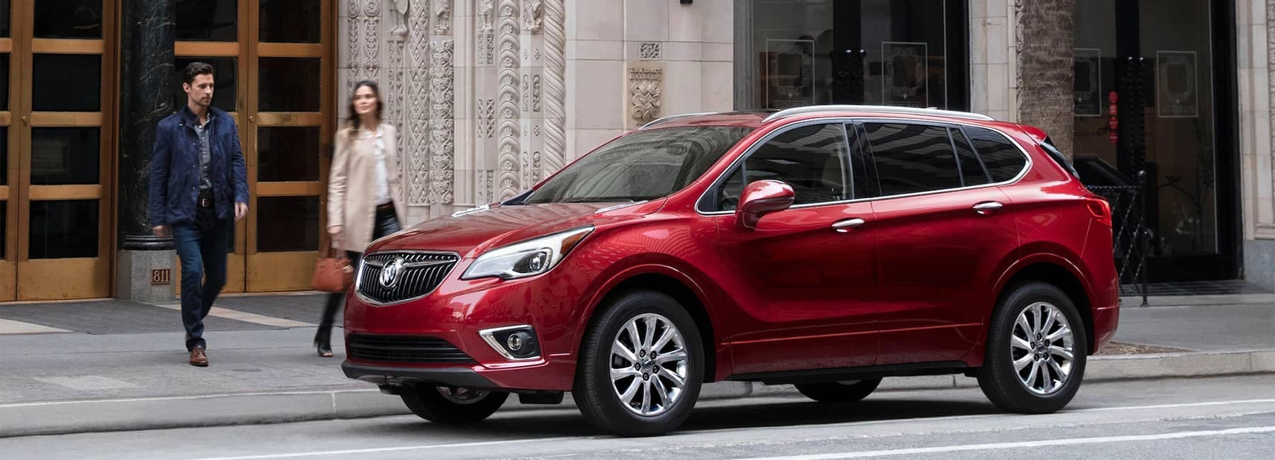 2020-Buick-Envision-Compact-SUV-with-Man-and-Woman-Walking