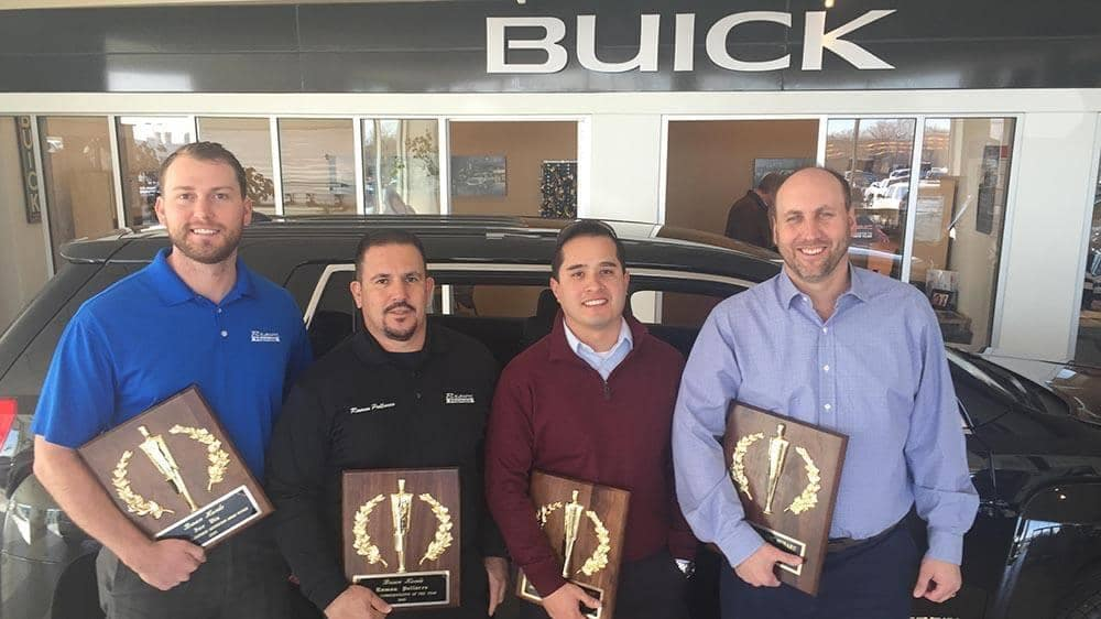 Brown Buick GMC employees holding awards