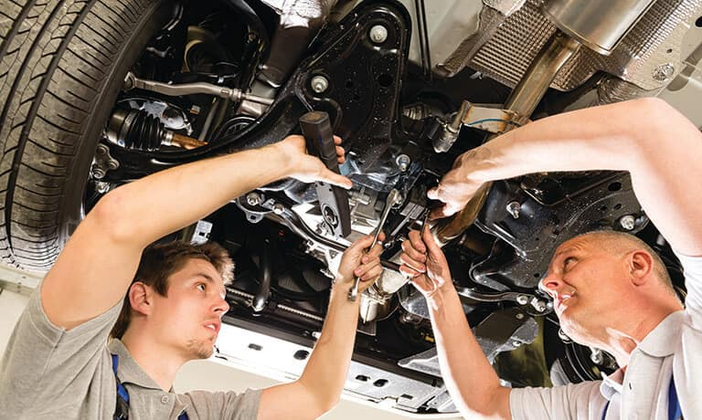 Two mechanics working under a car