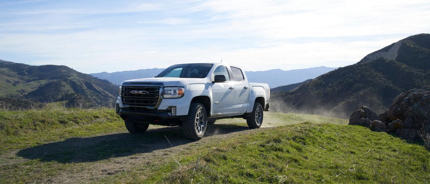 GMC Canyon in white exterior parked on grassy field