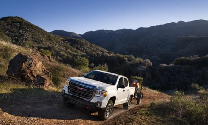 GMC Canyon in white exterior towing equipment on hill
