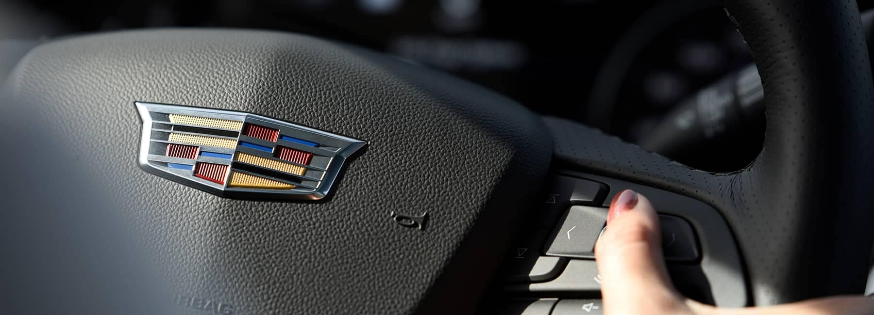 A close up photo of the Cadillac emblem on a steering wheel