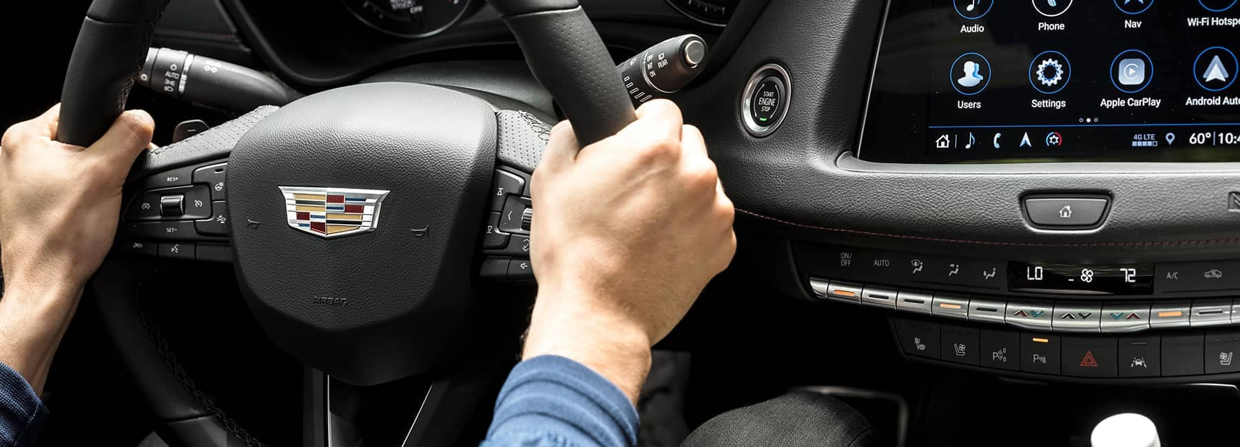person with their hands on steering wheel
