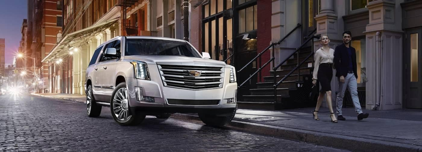 Cadillac Escalade parked on city street, couple walking by