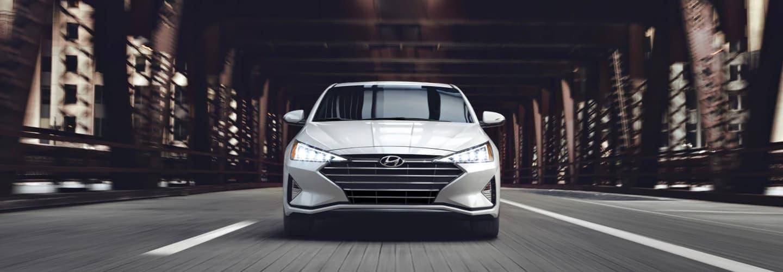 White Hyundai sedan driving under overpass