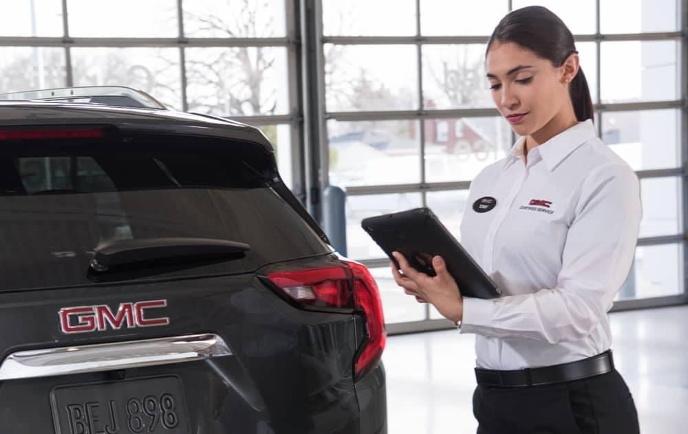 GMC Certified Service Female technician with tablet inspects vehicle exterior