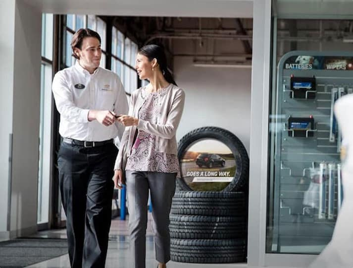 A dealership manager handing over a set of car keys to a lady.