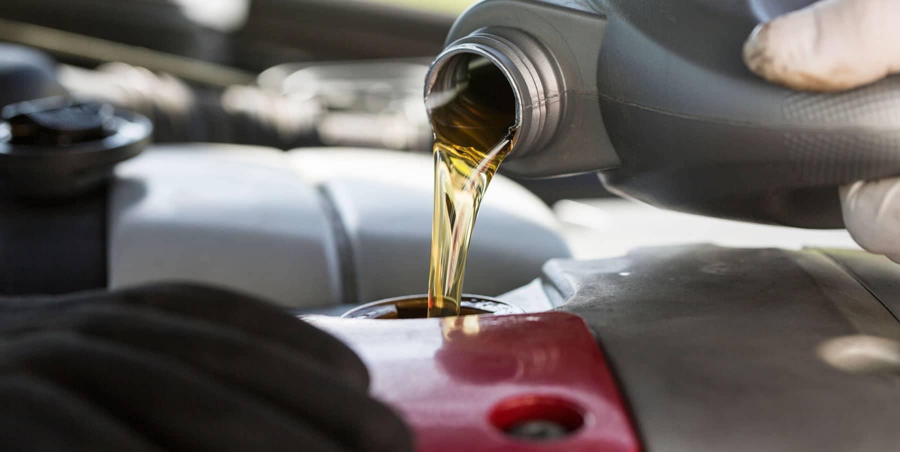 technician pours oil in car