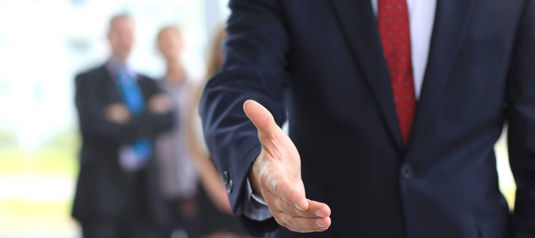 man in suit reaches out shake hands with staff in background