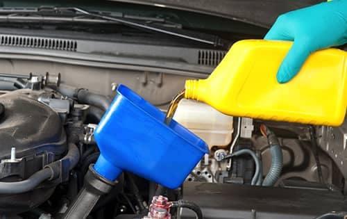 technician adding oil to car