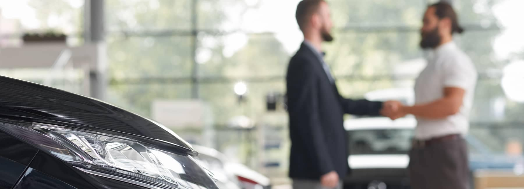 A car salesman and customer shake hands after agreeing on a purchase price