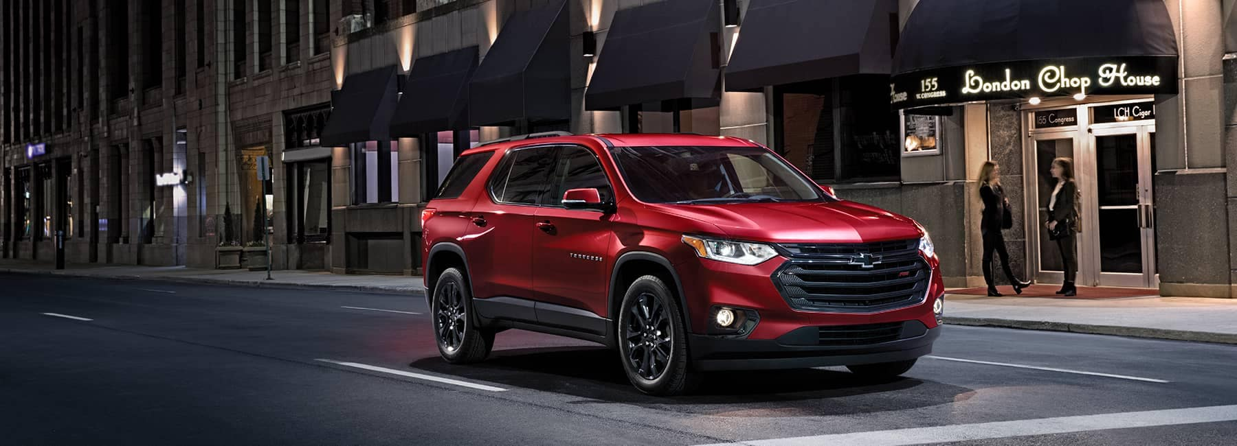 Red 2020 Chevrolet Traverse on a City St at Night