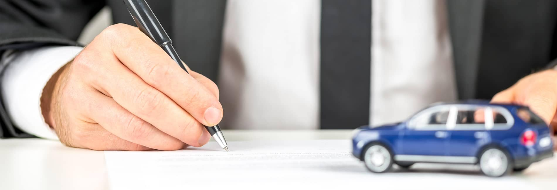 Man Signing Document with Blue Toy Car
