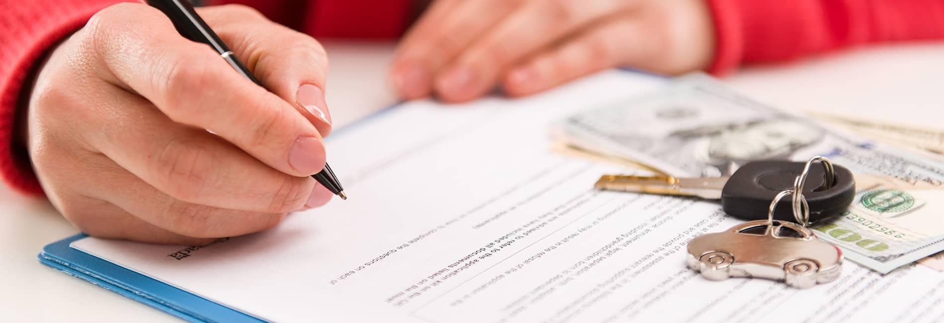 person filling out paperwork with keys on the table