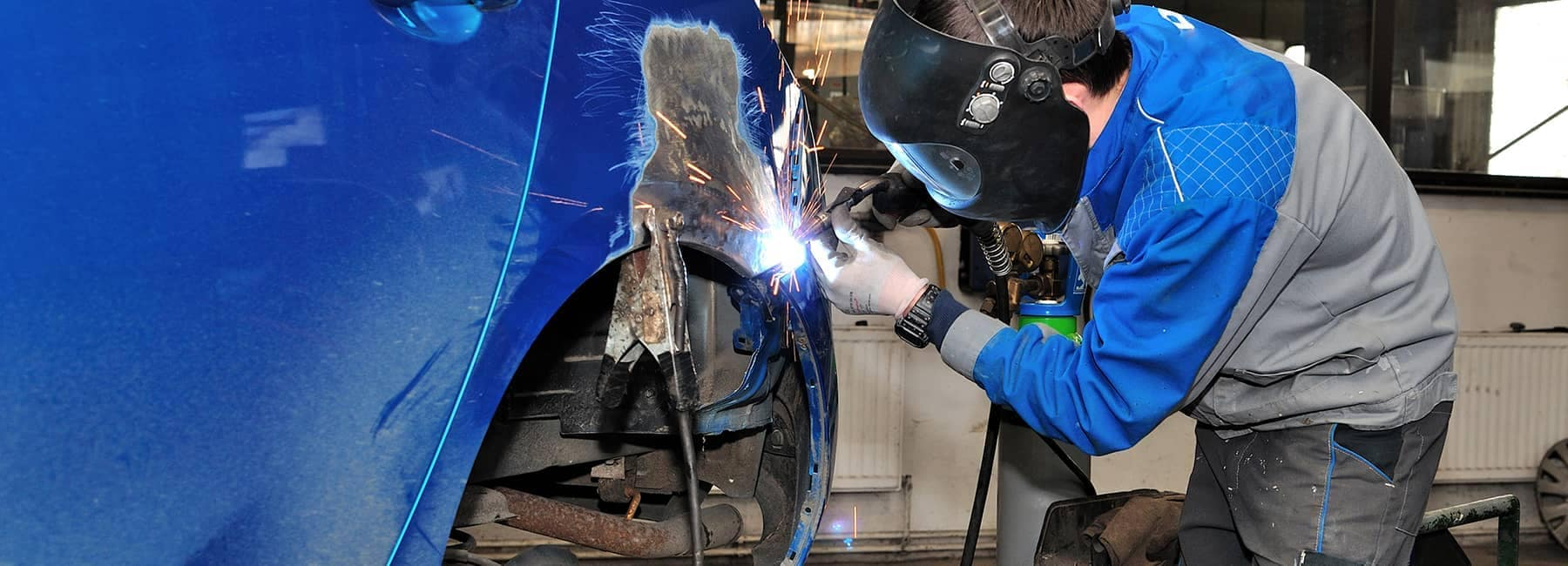 Body Shop technician working on repairing a blue vehicle