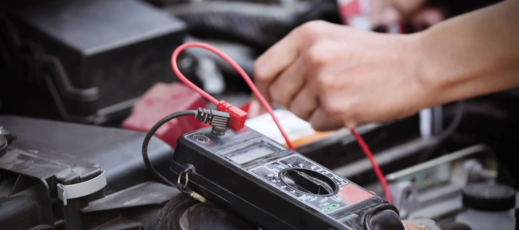 Battery picture of technician testing battery voltage