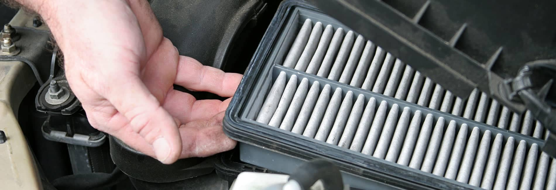 man's hand pulling out an air filter