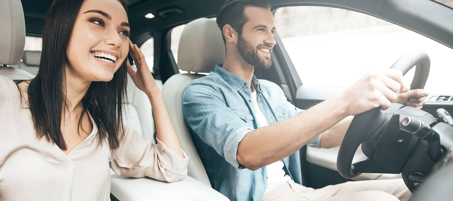 smiling couple in a car looking forward