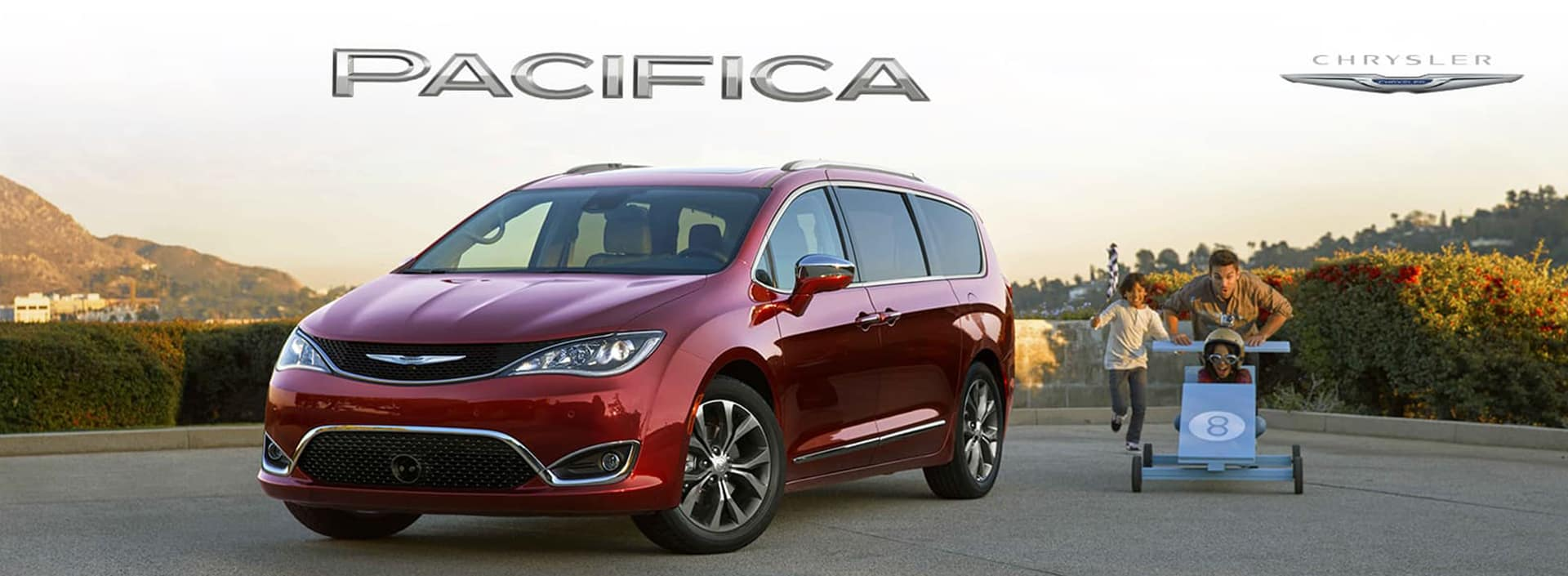 Chrysler Pacifica parked in a parking lot with a family right outside of it
