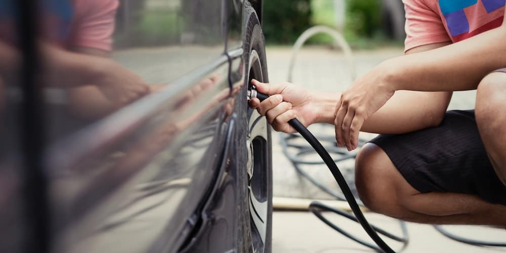 Man Filling Up Tire at Home