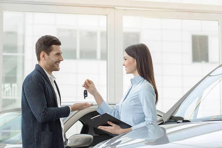 car rental agent hands customer car keys
