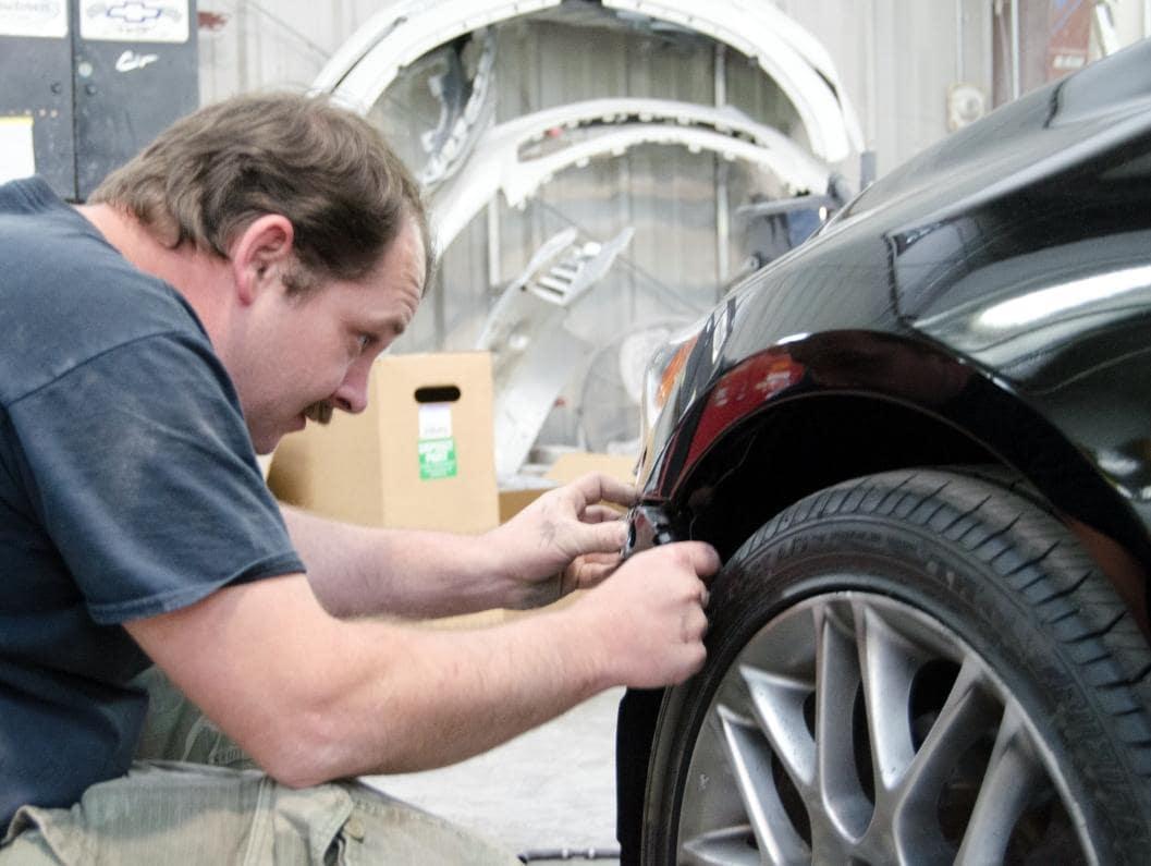 man repairs edge of front bumper